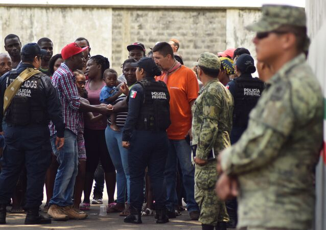 Migrants talk to police officers as soldiers, assigned to the newly created National Guard, keep watch outside the Siglo XXI immigrant detention center as part of the security measures by the federal government, in Tapachula, Mexico May 23, 2019. REUTERS/Jose Torres