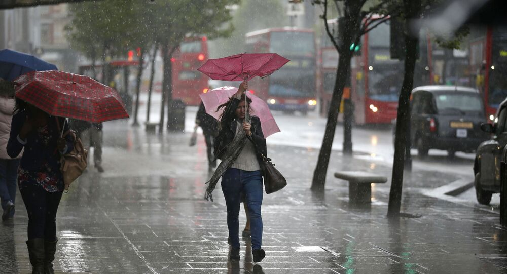 A woman's umbrella blown inside-out as she walks through a heavy rain shower on Oxford Street in London (File)