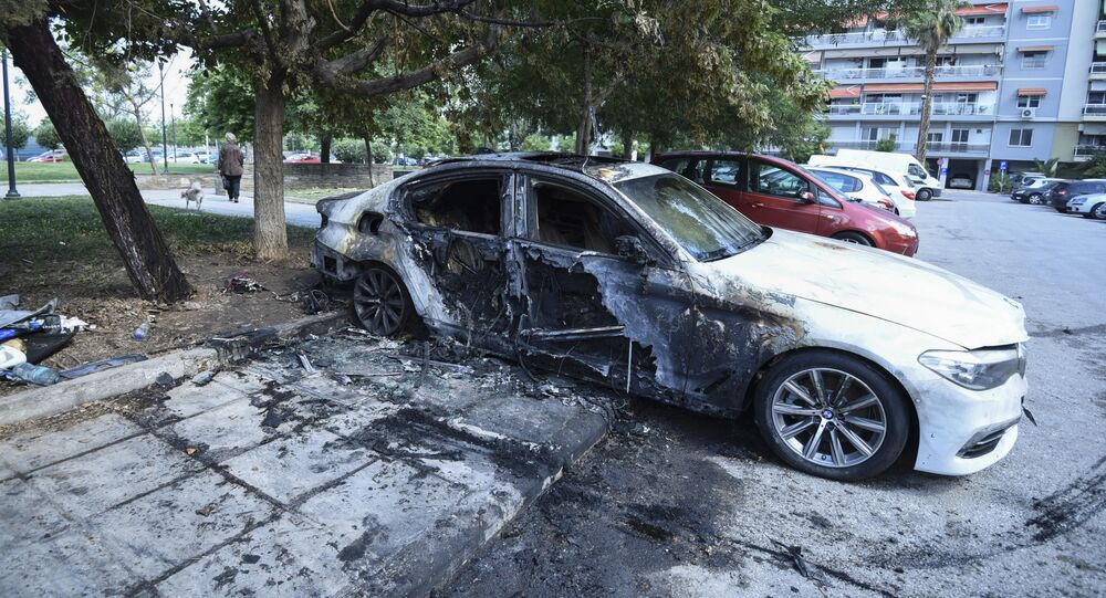 A damaged car belonging to a Turkish national is parked by a block of flats in the northern port city of Thessaloniki, Greece on Monday, June 10, 2019