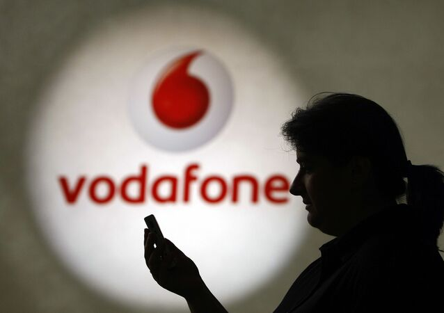 A woman looks at a mobile phone on 19 July ]2007, in Duesseldorf before a logo of the mobile operator Vodafone.