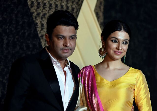 Indian Bollywood film producer Bhushan Kumar (L) with his wife actress Divya Khosla pose for a picture during the wedding reception of film producer Mukesh Bhatt's daughter Sakshi Bhatt, in Mumbai late on January 25, 2019