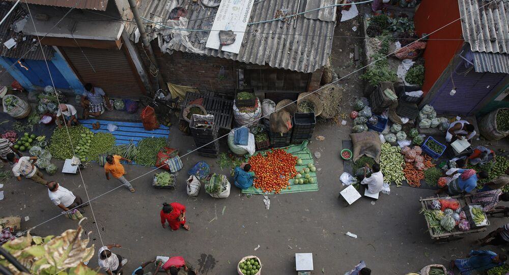 People shop at a roadside vegetable market in Kolkata, India, Tuesday, June 4, 2019.