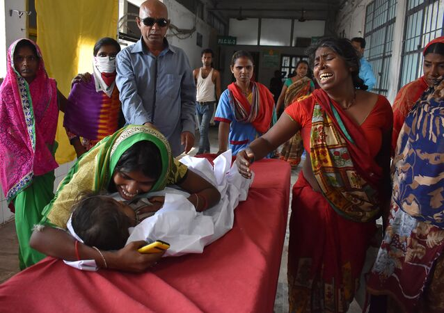An Indian child arrives in a hospital due to Acute Encephalitis Syndrome (AES) as family members react in Muzaffarpur on June 10, 2019
