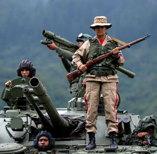A Venezuelan militia woman (front) and other troops in different fatigues and carrying various weapons stand on a Russian-made BMP-3M IFV during the press conference given by Defence Minister general Vladimir Padrino Lopez at Fort Tiuna in Caracas on August 14, 2017