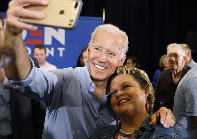 Former Vice President Joe Biden poses for a photo with a supporter in Clinton, Iowa