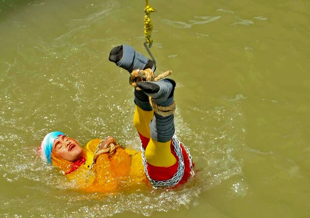 In this photo taken on June 16, 2019 Indian stuntman Chanchal Lahiri, known by his stage name Jadugar Mandrake, is lowered into the Ganges river, while tied up with steel chains and ropes, in Kolkata.