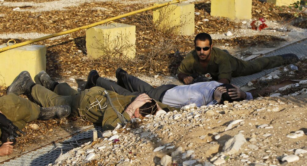 Israeli soldiers and a civilian take cover as a siren alerting of an incoming rocket from Gaza Strip sounds in Ofakim, southern Israel (File)