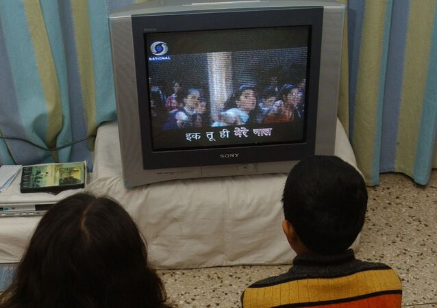 Indian children watch 'Rangoli' a Hindi film on television with subtitles in New Delhi (File)