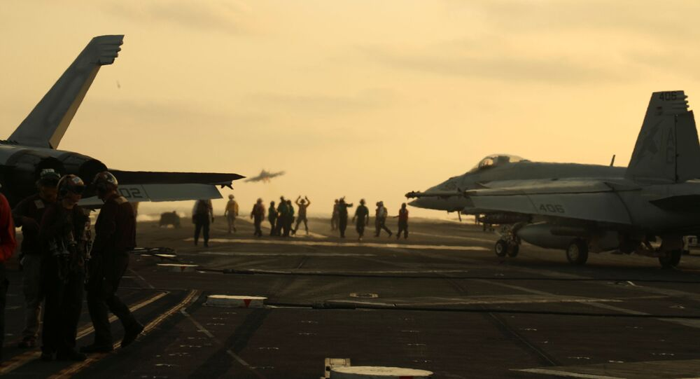 US Navy sailors launch an F/A-18 Super Hornet from the flight deck of the aircraft carrier USS Abraham Lincoln in the Arabian Sea, 3 June 2019