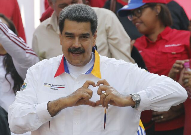 In this 20 May 2019 photo, Venezuela's President Nicolas Maduro flashes a hand-heart symbol to supporters outside Miraflores presidential palace in Caracas, Venezuela.