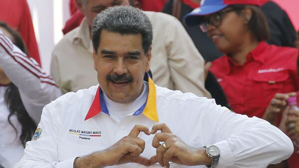In this May 20, 2019 photo, Venezuela's President Nicolas Maduro flashes a hand-heart symbol to supporters outside Miraflores presidential palace in Caracas, Venezuela. - Sputnik International