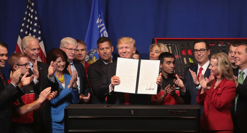 President Donald Trump signs an executive order to try to bring jobs back to American workers and revamp the H-1B visa guest worker program during a visit to the headquarters of tool manufacturer Snap-On on April 18, 2017 in Kenosha, Wisconsin