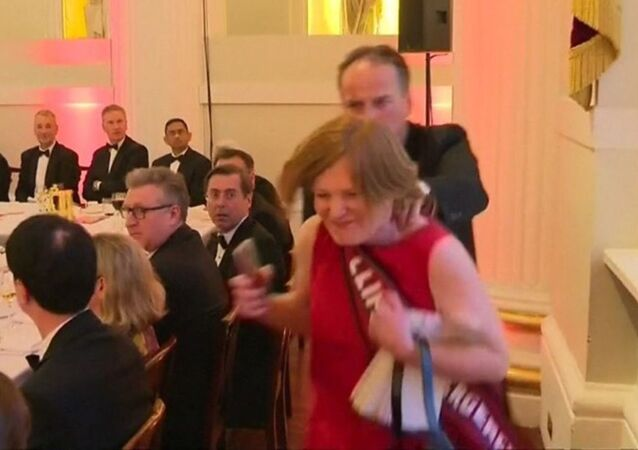 A screenshot of the video of Mark Field appearing to grab a female protester by her neck and haul her away