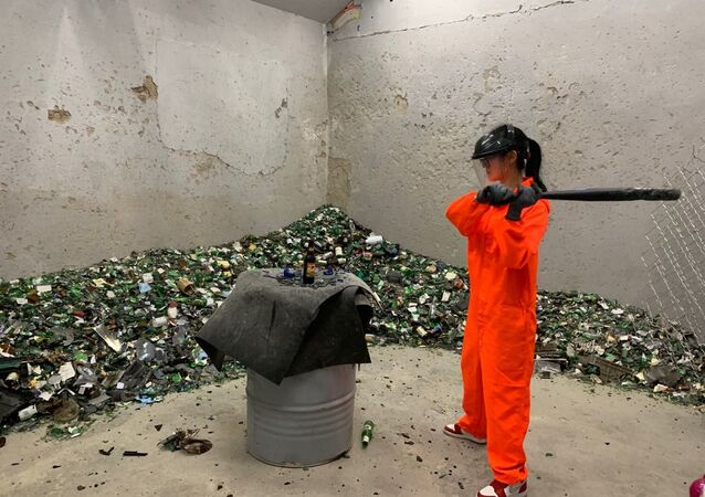 A fully-equipped woman is smashing a bottle in one of China's rage rooms