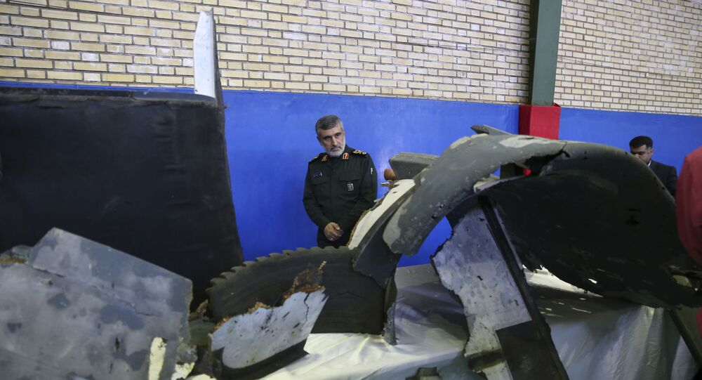 Head of the Revolutionary Guard's aerospace division Gen. Amir Ali Hajizadeh looks at debris from what the division describes as the U.S. drone which was shot down on Thursday, in Tehran, Iran, Friday, June 21, 2019