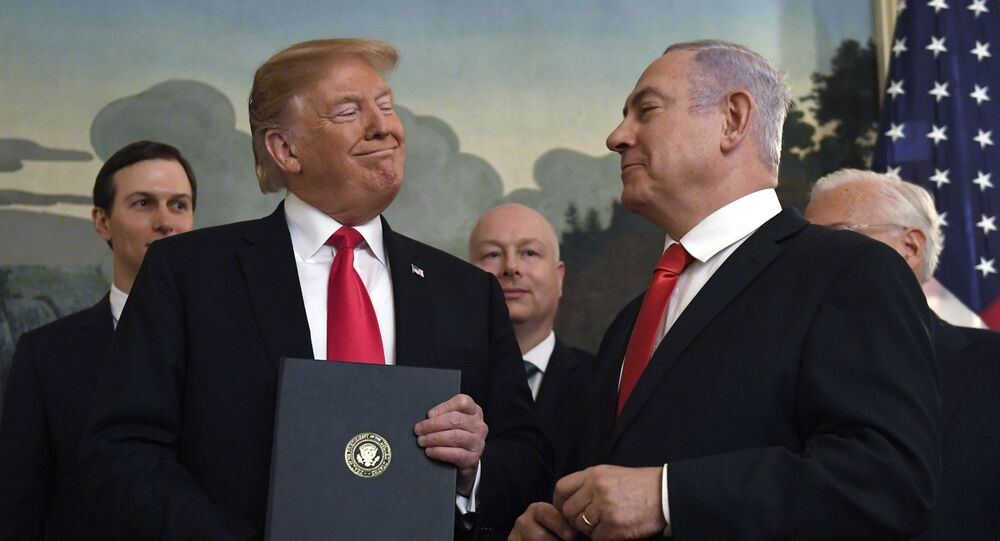 In this Monday, 25 March 2019 file photo, President Donald Trump smiles at Israeli Prime Minister Benjamin Netanyahu, right, after signing a proclamation in the Diplomatic Reception Room at the White House in Washington