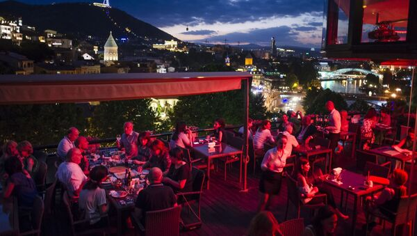 People rest at an open-air restaurant atop of a hill next to the Kura River in Tbilisi, Georgia - Sputnik International