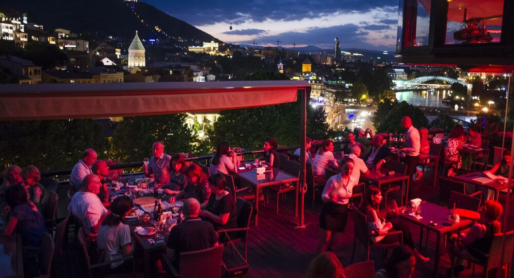 People rest at an open-air restaurant atop of a hill next to the Kura River in Tbilisi, Georgia