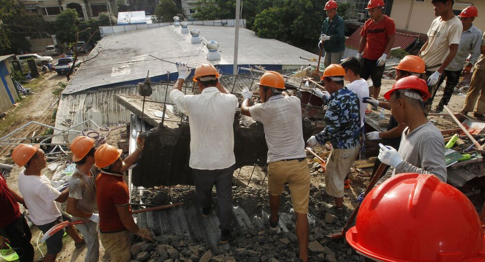 Rescuers try to remove the rubble at the site of a collapsed building in Preah Sihanouk province, Cambodia
