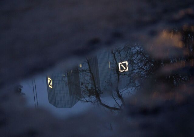 The Deutsche Bank headquarters is reflected in a puddle in Frankfurt, Germany, Monday, Jan. 20, 2014. Shares of Deutsche Bank AG have fallen sharply after Germany's biggest lender announced a large fourth-quarter net loss, its results weighed down by one-time expenses and losses on investments it is disposing of to strengthen its finances. The bank on Sunday night, Jan. 19, 2014 posted a fourth-quarter net loss of 965 million euros (US dollar 1.3 billion), an announcement that came 10 days before it was scheduled to release its results.