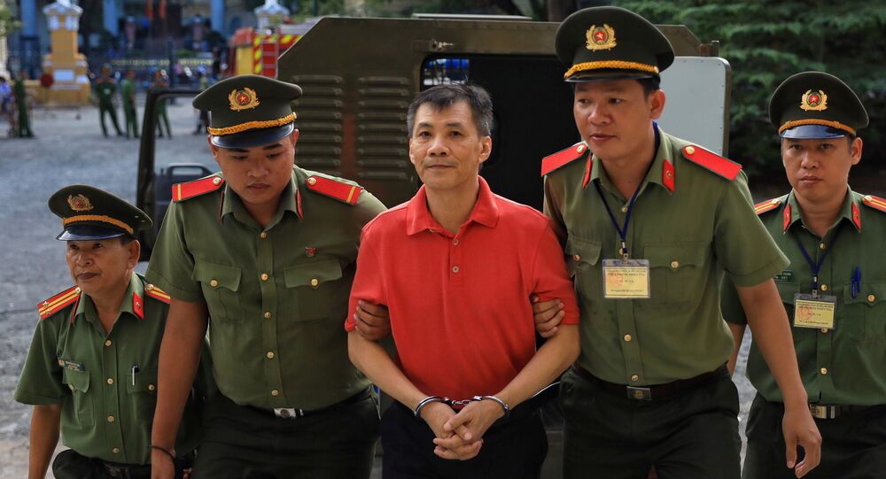 U.S. citizen Michael Nguyen is escorted by policemen before his trial at a court in Ho Chi Minh city, Vietnam June 24, 2019