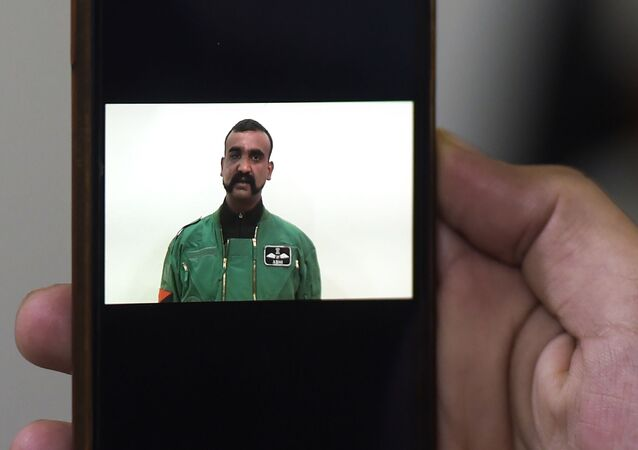 A Pakistani man watches the latest video statement released by Pakistan's military authorities of the Indian Wing Commander pilot Abhinandan Varthaman on his smartphone in Islamabad on March 1, 2019. - An Indian pilot shot down in a dogfight with Pakistani aircraft returned to India on March 1, after being freed in what Islamabad called a peace gesture following the two countries' biggest standoff in years. (Photo by AAMIR QURESHI / AFP)