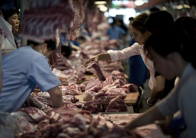 Customer buys pork meat inside a market in Beijing, China (File)