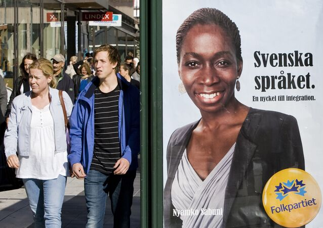Swedish people walk next to an election poster of Nyamko Sabuni from The Liberal People's Party, a central-right which advocates social liberalismin central Stockholm on September 9, 2010 ahead of the September 19 elections