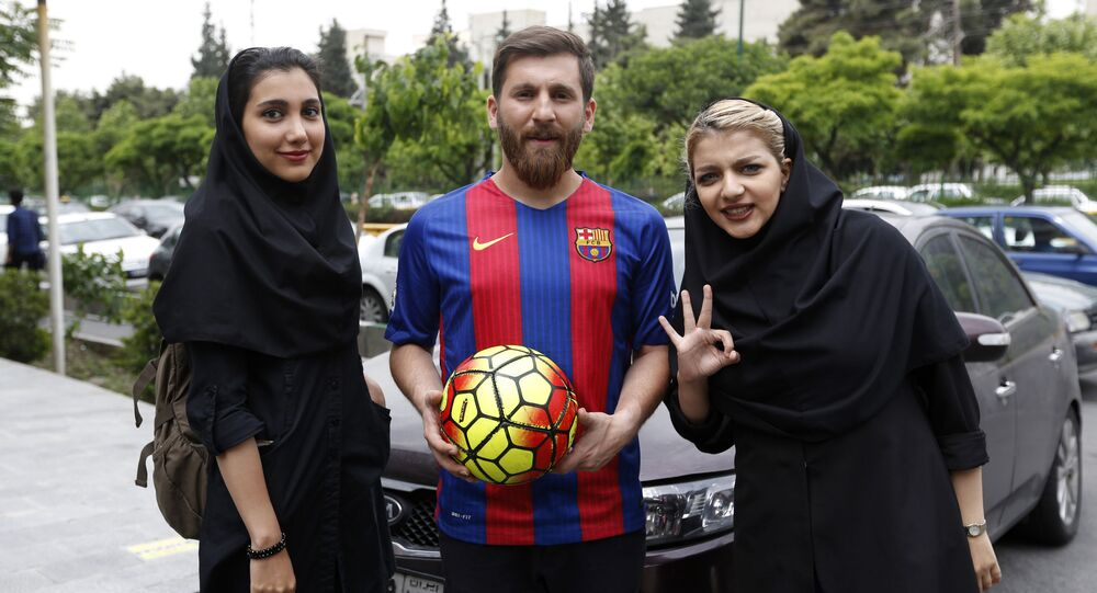 Reza Parastesh, a doppelganger of Barcelona and Argentina's footballer Lionel Messi, poses for a picture with fans in a street in Tehran on May 8, 2017