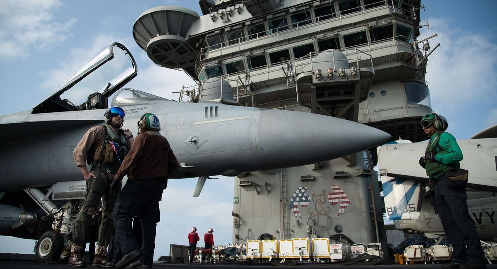 FILE - In this June 3, 2019 file photo, a pilot speaks to a crew member by an F/A-18 fighter jet on the deck of the USS Abraham Lincoln aircraft carrier in the Arabian Sea