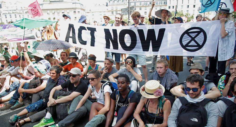French youth and environmental activists block a bridge during a demonstration to urge world leaders to act against climate change, in Paris, France, June 28, 2019