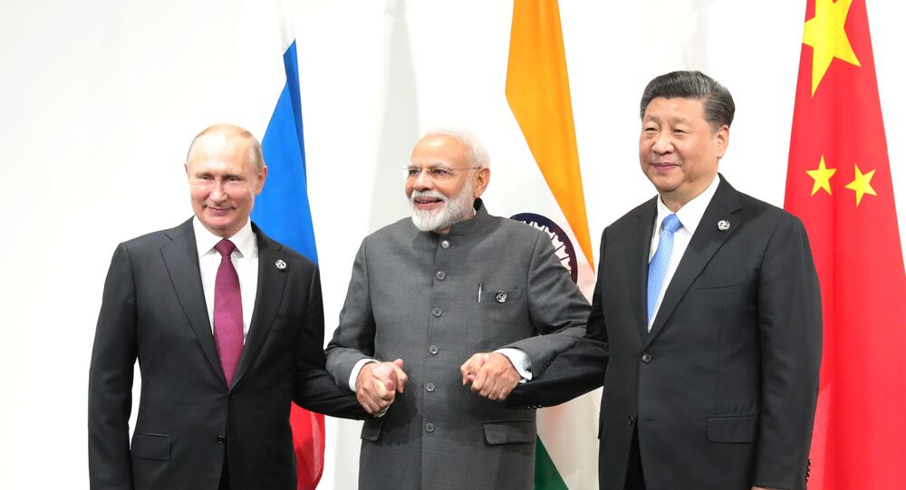 Russian President Vladimir Putin, India's Prime Minister Narendra Modi and Chinese President Xi Jinping pose for a photo during a meeting on the sidelines of the Group of 20 (G20) leaders summit in Osaka, Japan