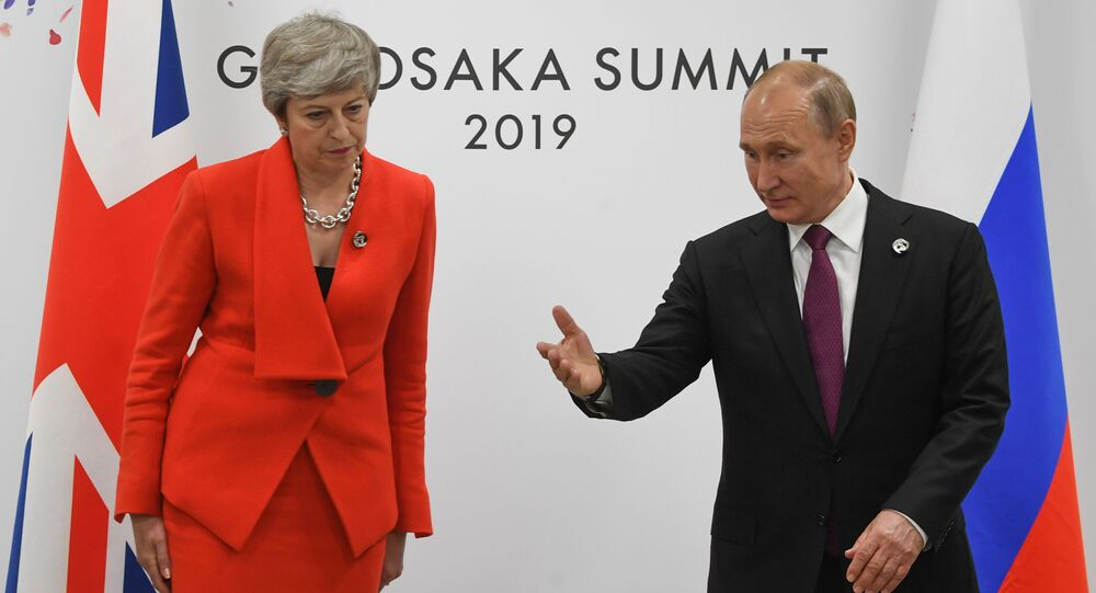 British Prime Minister Theresa May and Russian President Vladimir Putin take their seats during a meeting on the sidelines of the Group of 20 (G20) leaders summit in Osaka, Japan