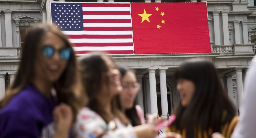 In this Thursday, Sept. 24, 2015, photo, China's flag is displayed next to the American flag on the side of the Old Executive Office Building on the White House complex in Washington, the day before a state visit by Chinese President Xi Jinping