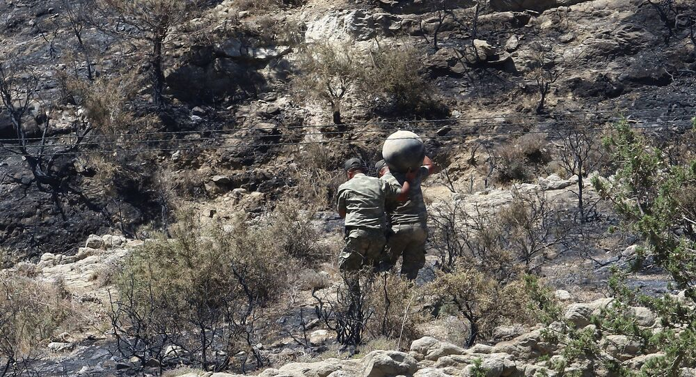 Military personnel carry debris on a slope where a missile struck, in Tashkent (also known as Vouno), in northern Cyprus, July 1, 2019