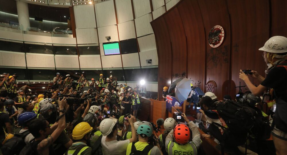 Protesters tie the British colonial flag to the parliament podium after they broke into the government headquarters in Hong Kong on July 1, 2019, on the 22nd anniversary of the city's handover from Britain to China.