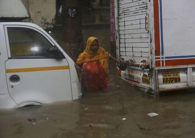 A woman tries to cross through a waterlogged street during monsoon rains in Mumbai