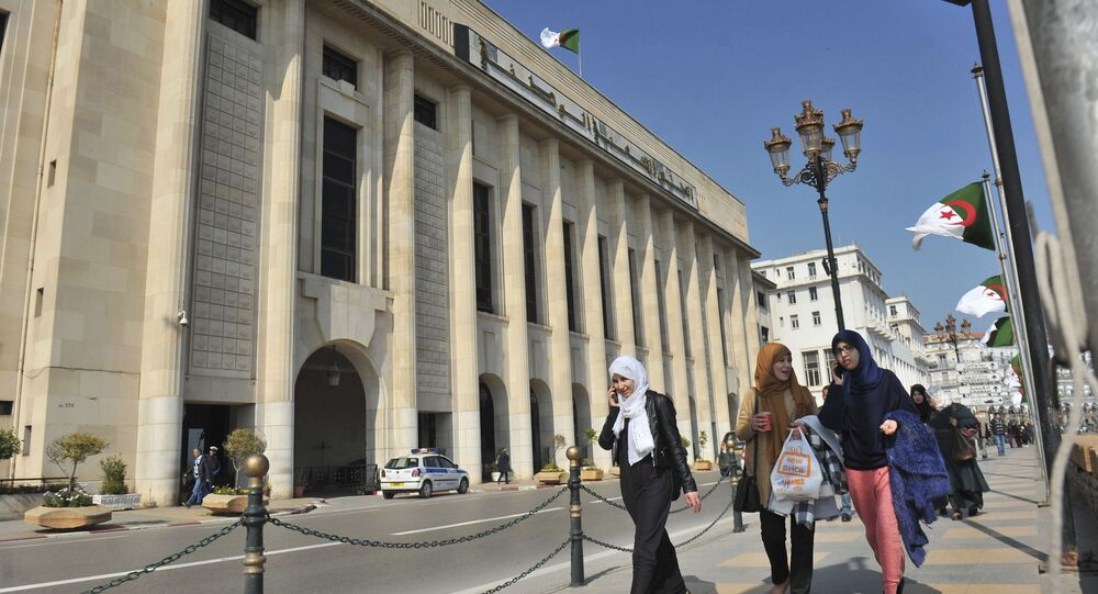 In this photo taken on Thursday, March 2, 2017, Algerian women pass by the People's National Assembly building in Algiers, Algeria
