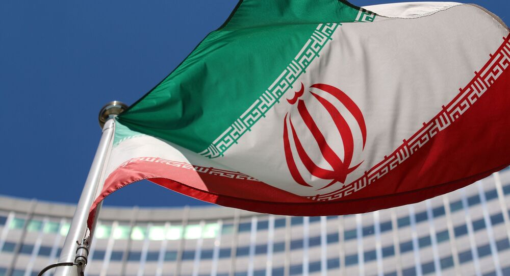 The Iranian flag flies in front of a UN building where closed-door nuclear talks take place at the International Center in Vienna, Austria, Wednesday, 18 June 2014