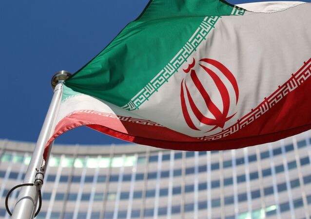 The Iranian flag flies in front of a UN building where closed-door nuclear talks take place at the International Center in Vienna, Austria, Wednesday, June 18, 2014