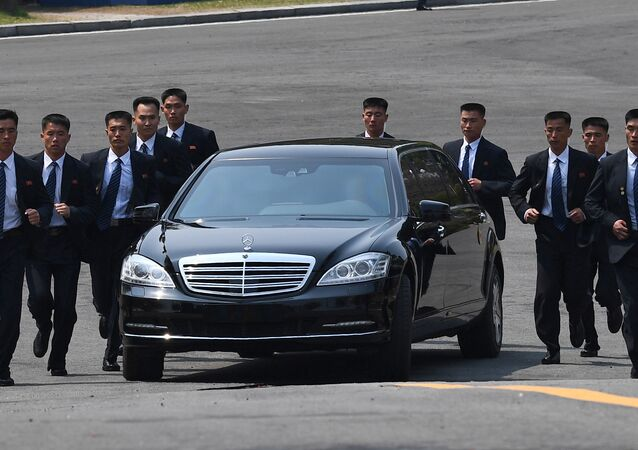 North Korean bodyguards jog next to a car carrying North Korea's leader Kim Jong Un returning to the North for a lunch break after a morning session of the inter-Korean summit at the truce village of Panmunjom on April 27, 2018