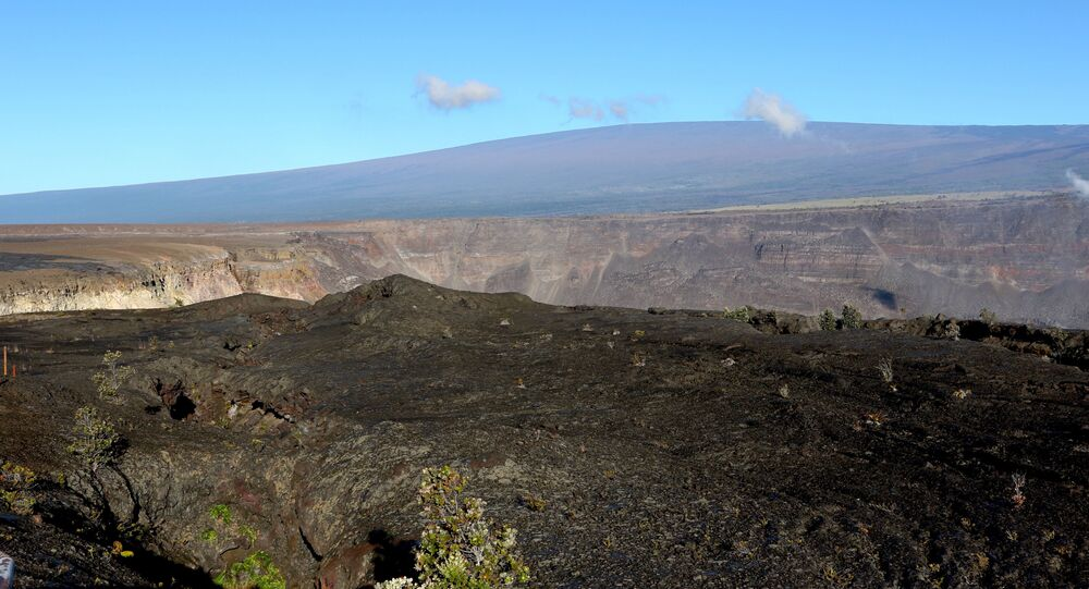 In this April 25, 2019 photo, Hawaii's Mauna Loa volcano, background, towers over the summit crater of Kilauea volcano in Hawaii Volcanoes National Park on the Big Island. Federal officials raised the alert level for Mauna Loa, the world's largest active volcano, Tuesday, July 2, 2019. The U.S. Geological Survey changed the level from normal to advisory after observing a slight increase in earthquakes and ground swelling over the past several months. Officials say the increased alert level does not mean an eruption is imminent. (AP Photo/Caleb Jones)