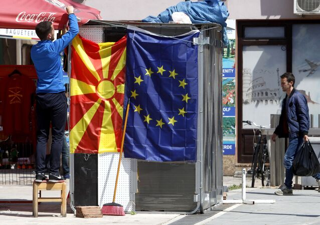 A street vendor fixes a North Macedonia flag next to an EU flag in a street in Skopje