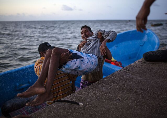 In this Sept. 4, 2018 photo, Saul Ronaldo Atiliano, 45, is carried by comrades while arriving to Puerto Lempira, Honduras, after suffering decompression syndrome while fishing for lobsters in the ocean.
