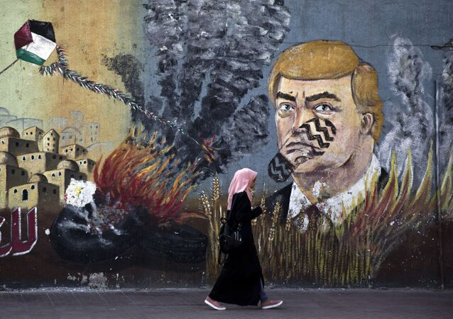 A wall with graffiti depicts U.S. President Donald Trump with a footprint on his face in Gaza City, Tuesday, June 25, 2019