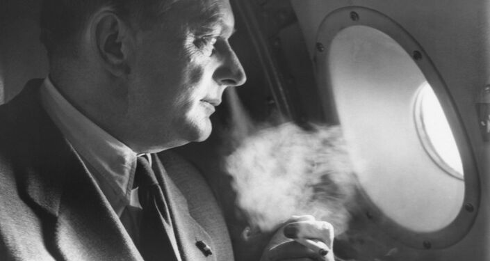 Dr Balint Rozza, a Hungarian refugee, blows a cloud of smoke from his cigarette on a plane to the US in 1956