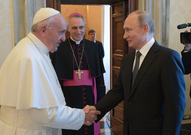 Russian President Vladimir Putin shakes hands with Pope Francis during their meeting at the Vatican. Archbishop Georg Ganswein is second left. Putin is on one-day official visit to Italy
