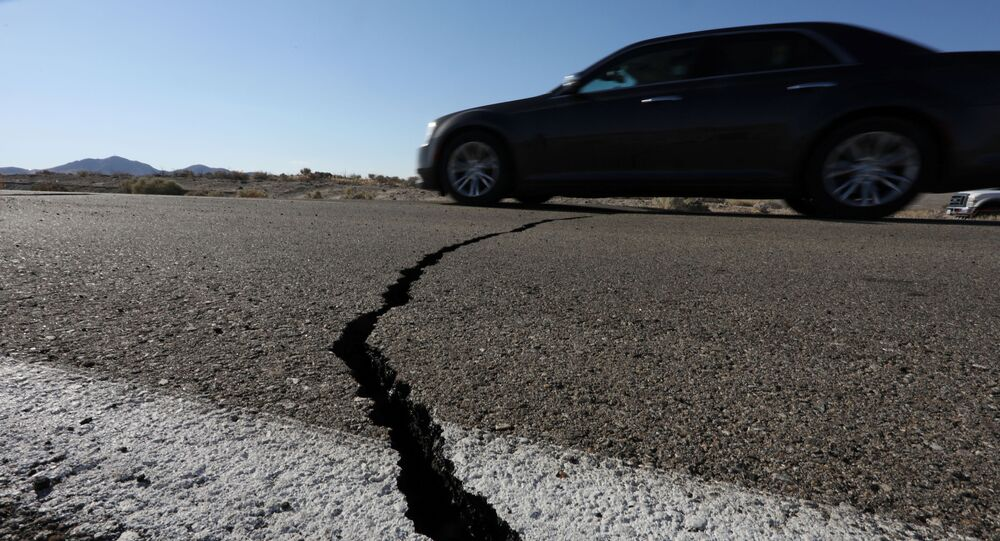 A car passes over a fissure that opened on a highway during a powerful earthquake that struck Southern California, near the city of Ridgecrest, California, U.S., July 4, 2019.
