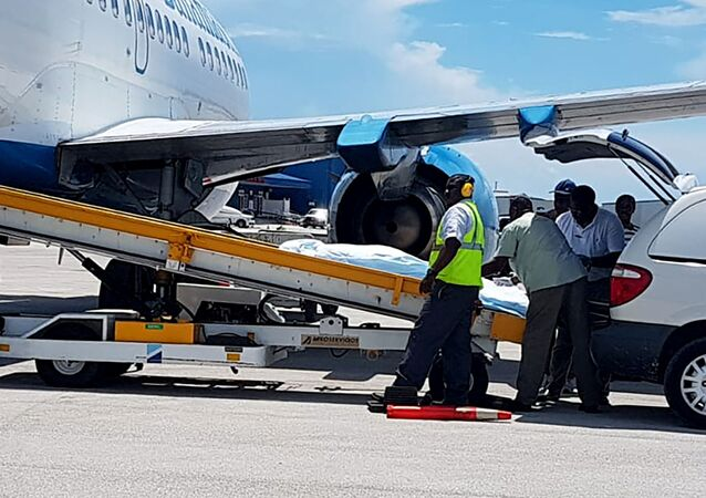 In this handout photo released by the Bahamas ZNS Network, employees oversee the arrival of the bodies of four women and three men, including billionaire coal entrepreneur Chris Cline and his daughter, at the airport in Nassau, Bahamas