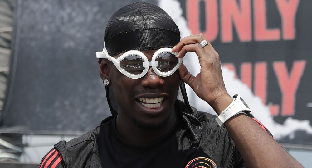 Manchester United's soccer player Paul Pogba, adjusts his goggles, given by a fan, during a meeting with his fans following a media day in Seoul, South Korea, Thursday, June 13, 2019. Pogba is in Seoul as a part of his Asian tour